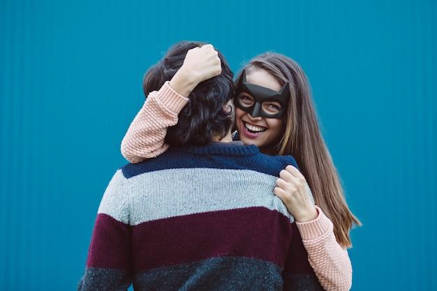 Ragazza in una maschera che bacia il suo giovane ragazzo.