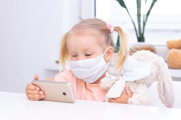 Ragazza in una maschera protettiva con un coniglietto giocattolo che utilizza un telefono cellulare, uno smartphone per le videochiamate, parla con i parenti, una ragazza siede a casa, una webcam per computer online, una videochiamata.