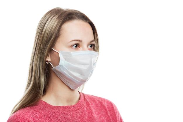 Ragazza in una mascherina medica. precauzioni durante il periodo della pandemia di coronavirus. prevenzione delle reazioni allergiche. isolato su un muro bianco avvicinamento. vista laterale. spazio per il testo.