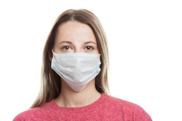 Ragazza in una mascherina medica. precauzioni durante il periodo della pandemia di coronavirus. prevenzione delle reazioni allergiche. isolato su un muro bianco avvicinamento.