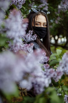 Ragazza in una mascherina medica su una priorità bassa dei lillà di fioritura. maschera nera. protezione da virus, influenza. protezione dal coronavirus. epidemia di coronavirus
