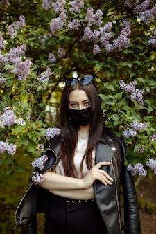 Ragazza in una mascherina medica su una priorità bassa dei lillà di fioritura. maschera nera. protezione da virus, influenza. protezione dal coronavirus.