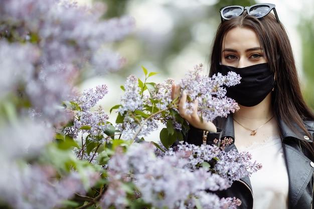 Ragazza in una mascherina medica su una priorità bassa dei lillà di fioritura. maschera nera.