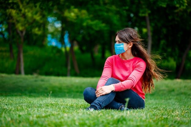 Ragazza in una mascherina medica sulla natura. ragazza che riposa nel parco dopo la quarantena covid-19