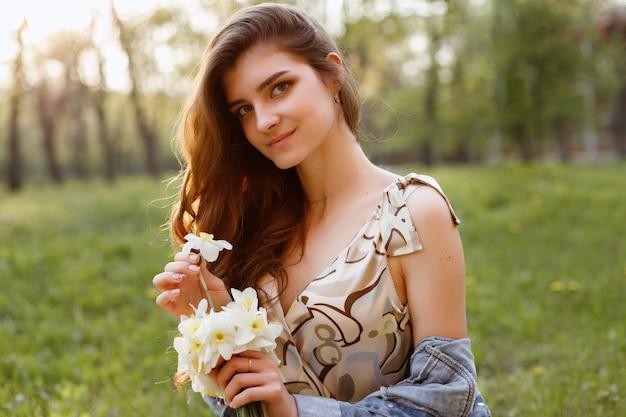 Ragazza in una passeggiata estiva con fiori. bei capelli ricci. ritratto. spazio sfocato