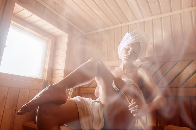 Ragazza in una sauna finlandese facendo peeling cutaneo