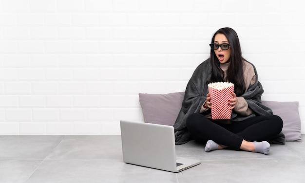 Ragazza in una stanza sorpresa con gli occhiali 3d e in possesso di un grande secchio di popcorn