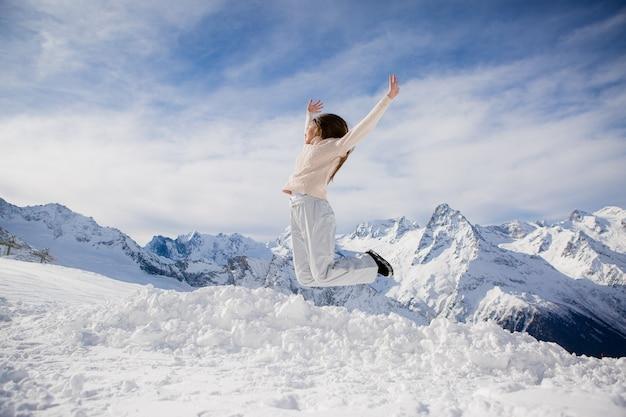 Ragazza in una tuta invernale guardando le montagne