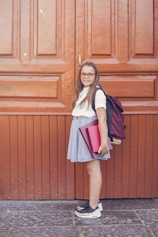Ragazza in uniforme scolastica con zaino prima di grandi porte