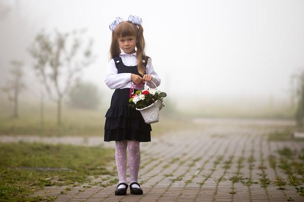 Ragazza in uniforme scolastica e fiocchi bianchi con fiori