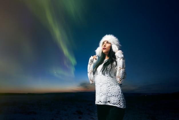 Ragazza in vestiti alla moda su fondo dell'aurora boreale ,.