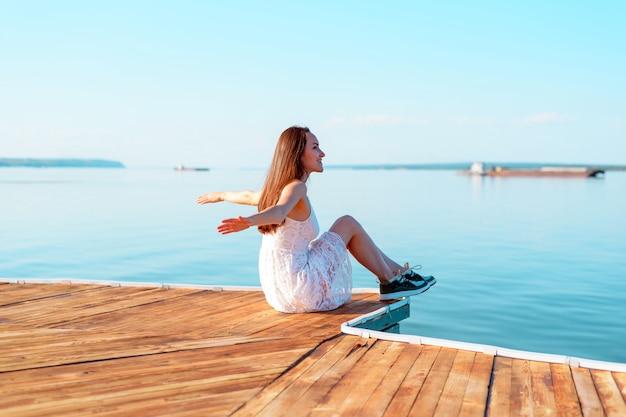 Ragazza in vestito bianco che si siede su un pilastro di legno con le mani aperte che esaminano la distanza del mare, libertà, aria pulita, sogni