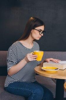 Ragazza in vetri che legge un libro in una caffetteria