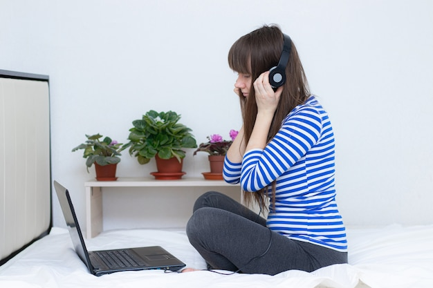 Ragazza incinta con un computer portatile sul letto.
