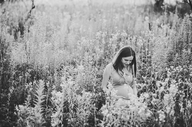 Ragazza incinta felice si siede e tiene le mani sullo stomaco, seduto sull'erba verde nel campo all'aperto.