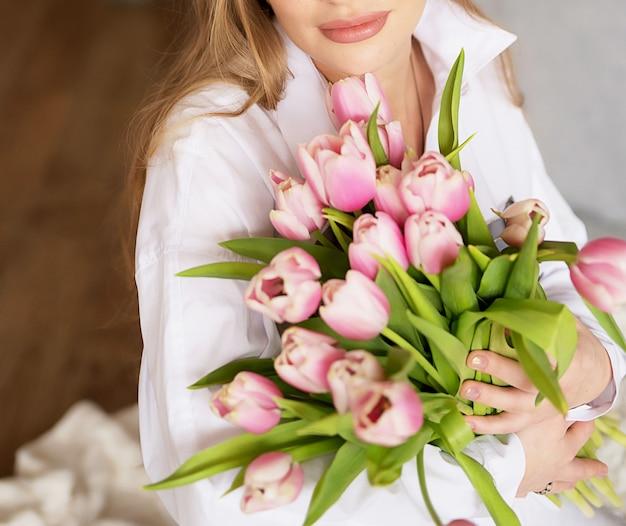 Ragazza incinta su uno sfondo chiaro con fiori. foto senza volto nella cornice.