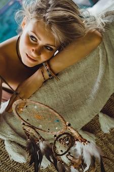 Ragazza indiana a casa cattura sogni. bella ragazza bionda con acchiappasogni.