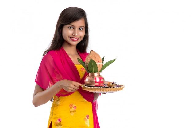 Ragazza indiana in possesso di un tradizionale kalash in rame con pooja thali, festival indiano, kalash in rame con cocco e foglia di mango con decorazioni floreali, essenziale in hindu pooja.