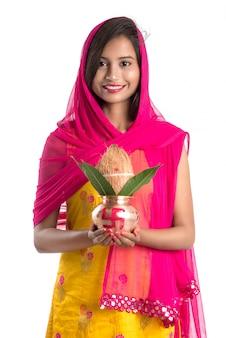 Ragazza indiana in possesso di un tradizionale kalash in rame, festival indiano, kalash in rame con foglie di cocco e mango con decorazioni floreali, essenziale in hindu pooja.