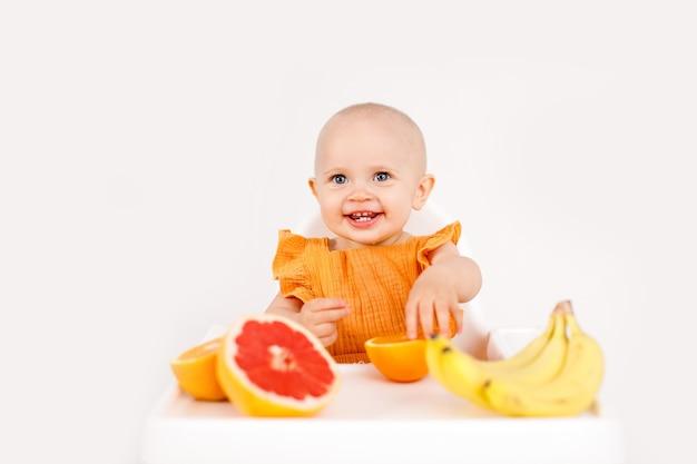 Ragazza infantile che si siede nella sedia del bambino alto che mangia frutta su bianco