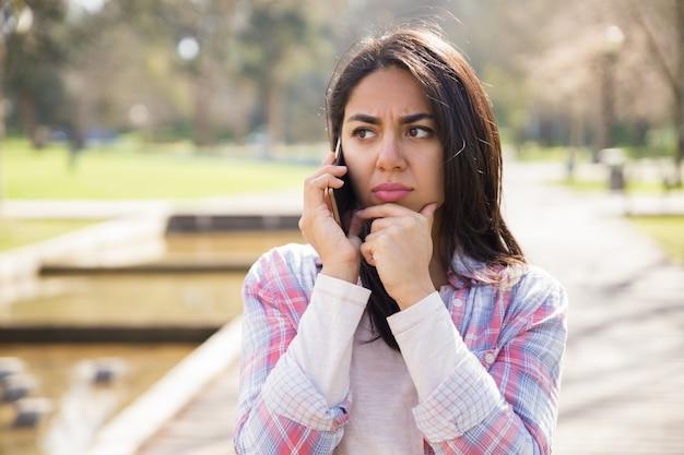 Ragazza infelice turbata che discute cattive notizie sul telefono