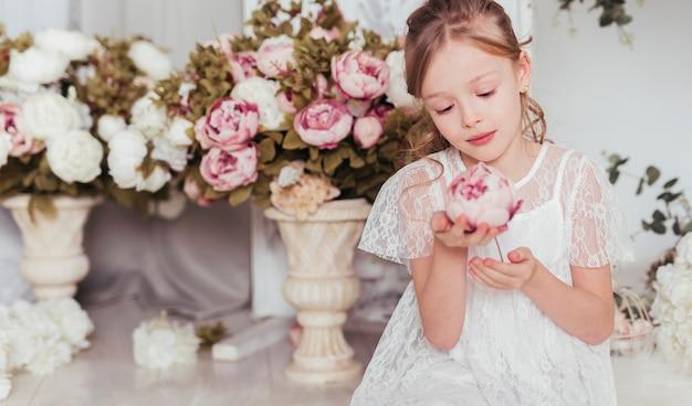 Ragazza innocente che esamina fiore