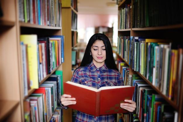 Ragazza intelligente che osserva in una biblioteca o archivia il libro o le informazioni desiderati. preparazione per l'esame