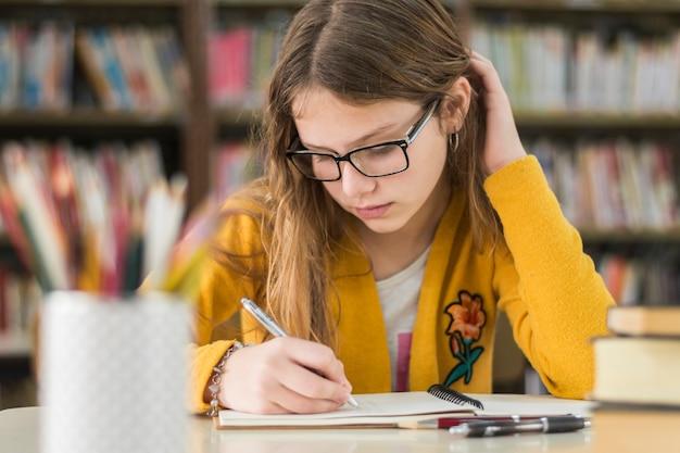 Ragazza intelligente che studia in biblioteca