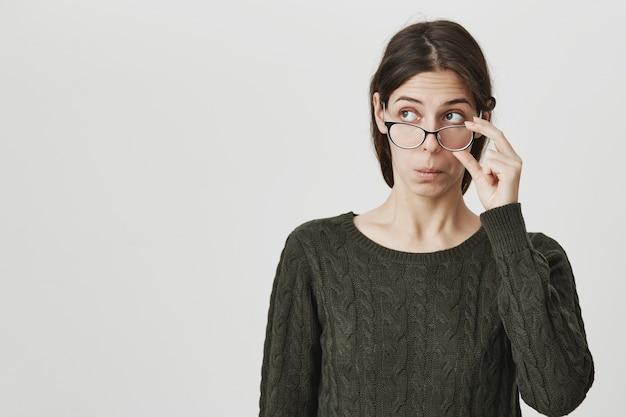 Ragazza intelligente con gli occhiali alla ricerca nell'angolo in alto a sinistra incuriosita, sbirciando