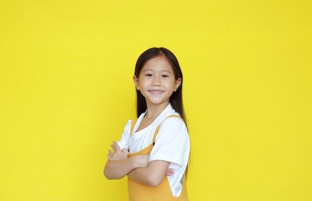 Ragazza intelligente con le braccia incrociate su uno sfondo giallo