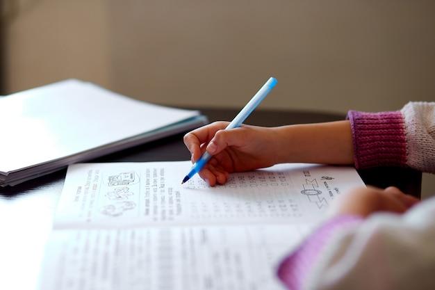 Ragazza irriconoscibile che fa i compiti, scrivendo il concetto di istruzione, quarantena della scuola domestica di coronavirus. una scuola a casa.
