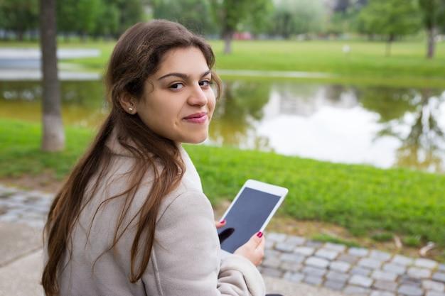 Ragazza latina positiva che chiacchiera online all'aperto
