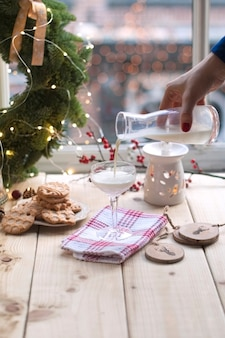 Ragazza latte in un bicchiere al tavolo vicino alla finestra, biscotti su un piatto e una corona di alberi di natale