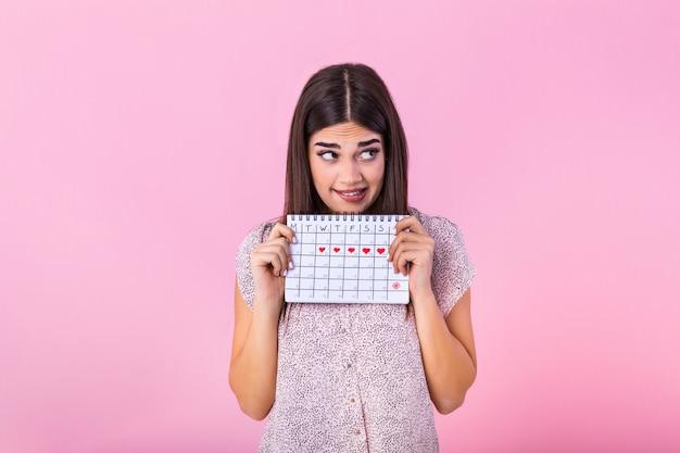 Ragazza magra imbarazzata che tiene calendario mestruale