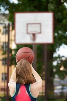 Ragazza magra rossa che lancia una palla nel canestro da basket all'aperto