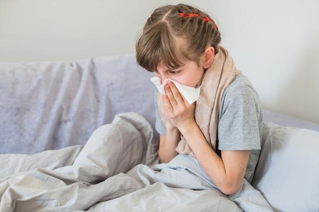 Ragazza malata che soffia il naso