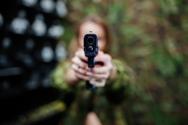 Ragazza militare in uniforme mimetica con la pistola a portata di mano contro il fondo dell'esercito su poligono di tiro. concentrati sulla pistola.