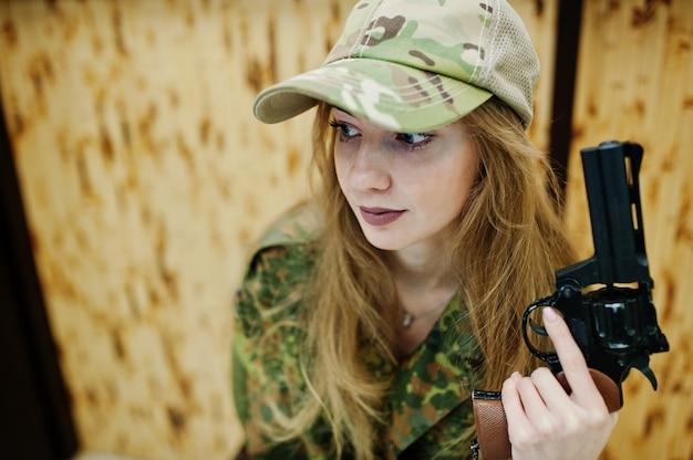 Ragazza militare in uniforme mimetica con pistola revolver a portata di mano su sfondo di esercito su poligono di tiro.