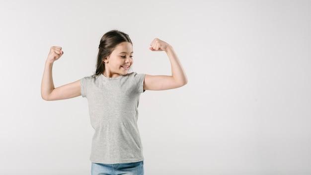 Ragazza minore che mostra i muscoli in studio