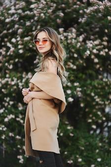 Ragazza modella bionda alla moda e sensuale in cappotto senza maniche e occhiali da sole alla moda