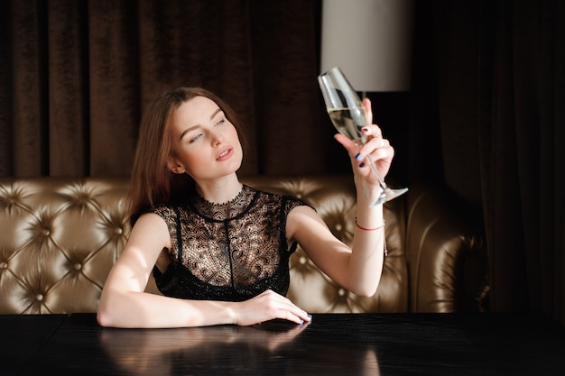 Ragazza modello sexy con un bicchiere di champagne alla festa.