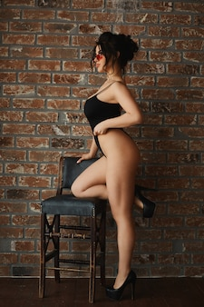 Ragazza modello sexy taglie forti, donna bruna alla moda con un grande busto, occhiali da sole e tute nere sexy, appoggiata allo sgabello e in posa all'interno del loft di fronte a un muro di mattoni