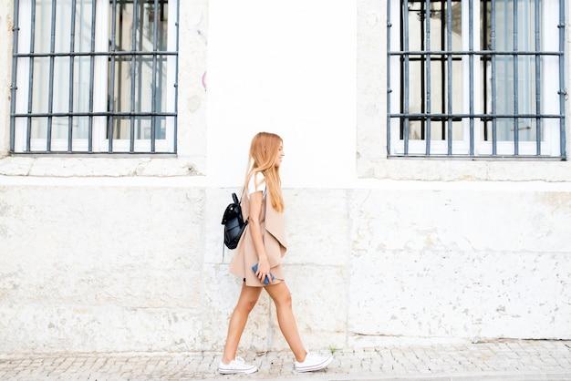 Ragazza moderna dei pantaloni a vita bassa che si muove lungo la via della città