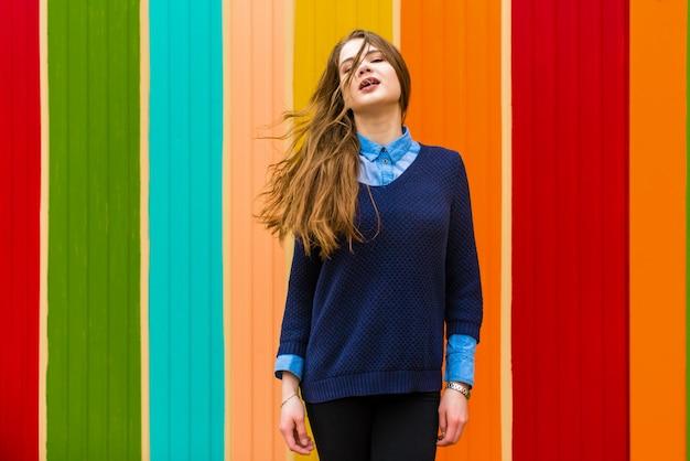 Ragazza molto bella su uno sfondo di parete colorata