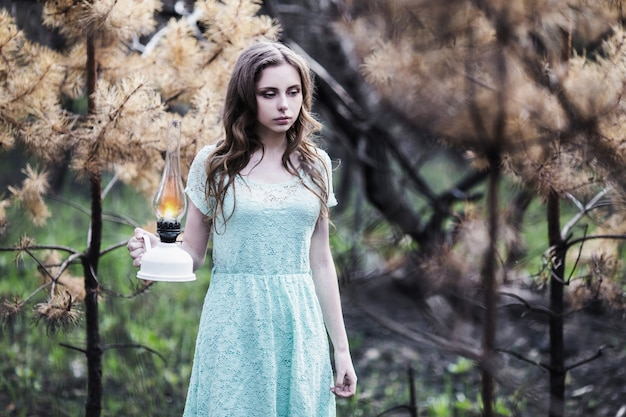 Ragazza molto carina con una lampada a cherosene. aspetto bambola. donna con capelli castani in un vestito turchese sulla natura. capelli lunghi. luce naturale. modello in posa sulla natura. lampada in mano. perso nella foresta