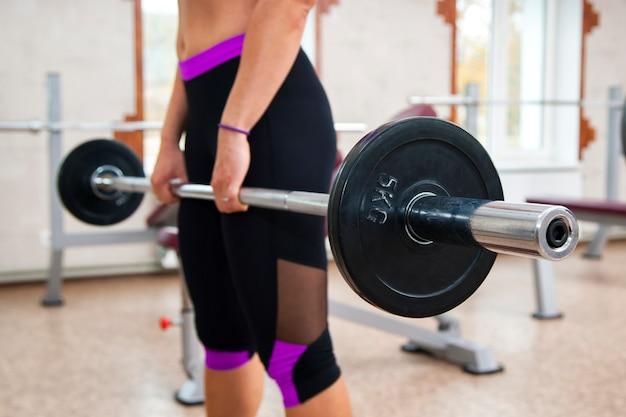 Ragazza muscolare di forma fisica che fa esercizio pesante del deadlift in palestra