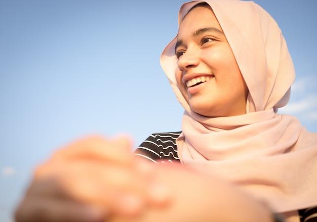 Ragazza musulmana con hijab sulla spiaggia durante le vacanze estive
