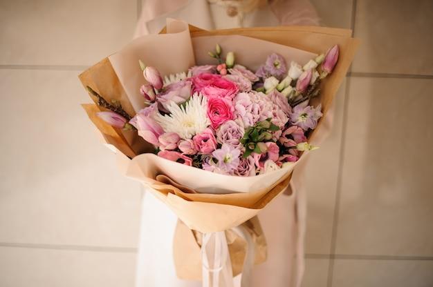 Ragazza nel cappotto che tiene un mazzo di fiori teneri di colore rosa