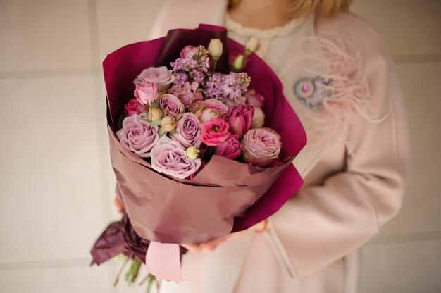 Ragazza nel cappotto che tiene un mazzo di fiori viola viola