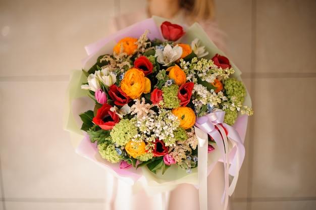 Ragazza nel cappotto che tiene un mazzo di teneri fiori rossi, arancioni e verdi